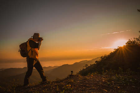 Young professional traveler man with camera shooting outdoor, fantastic mountain landscape 免版税图像