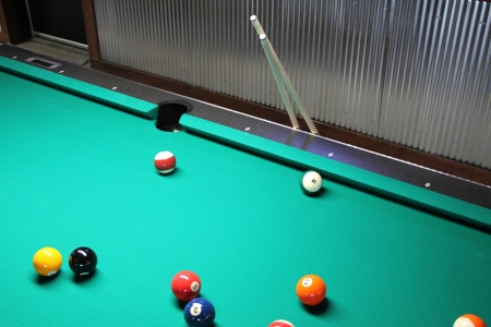 pool cues: A Game of Pool In Progress with Cues - A Game of 8 Ball in Progress on Pool Table with Cues Stock Photo