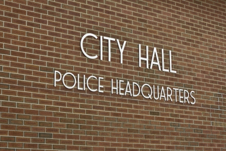 mayoral: City Hall   Police Headquarters - Simple City Hall - Police Headquarters Sign Against Brick Background