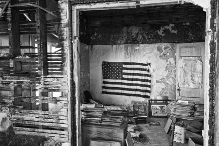 米国旗で放棄された建物全体 - 放棄されたマンションのスラム街のゴミ箱の上の米国旗
