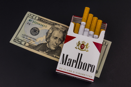 Indianapolis - Circa August 2016: Marlboro Cigarettes and Twenty Dollar Bills Representing the High Costs of Smoking. Marlboro is a product of the Altria Group XI Editorial
