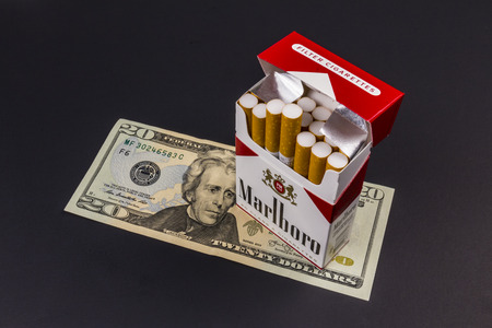 indianapolis: Indianapolis - Circa August 2016: Marlboro Cigarettes and Twenty Dollar Bills Representing the High Costs of Smoking. Marlboro is a product of the Altria Group VII