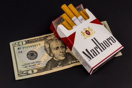 morris: Indianapolis - Circa August 2016: Marlboro Cigarettes and Twenty Dollar Bills Representing the High Costs of Smoking. Marlboro is a product of the Altria Group V