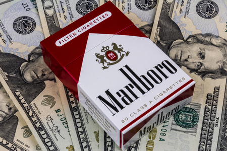 Indianapolis - Circa August 2016: Pack of Marlboro Cigarettes and Twenty Dollar Bills Representing the High Costs of Smoking. Marlboro is a product of the Altria Group III