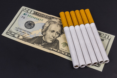 Indianapolis - Circa August 2016: Marlboro Cigarettes and Twenty Dollar Bills Representing the High Costs of Smoking. Marlboro is a product of the Altria Group IX