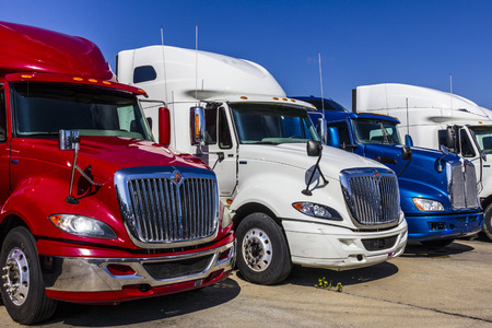 Indianapolis - Circa September 2017: Colorful Red, White and Blue Semi Tractor Trailer Trucks Lined up for Sale XVIII 新闻类图片