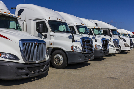 Indianapolis - Circa September 2017: White Semi Tractor Trailer Trucks Lined up for Sale XVII