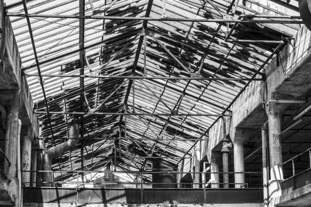 Interior of an abandoned factory in black and white. Broken glass and crumbling cement mark a once busy factory I