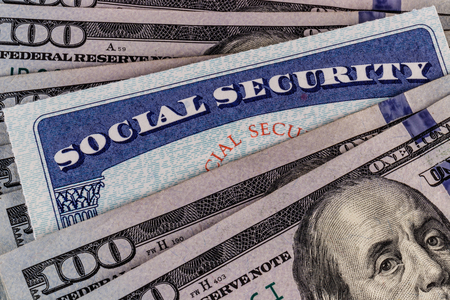 Social Security card and a bed of money representing the high cost of living on a fixed income