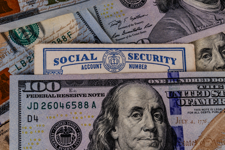 Old Social Security card and a bed of money representing the high cost of living on a fixed income III