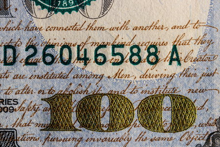 Closeup of the golden 100 and script on a one hundred dollar bill for background