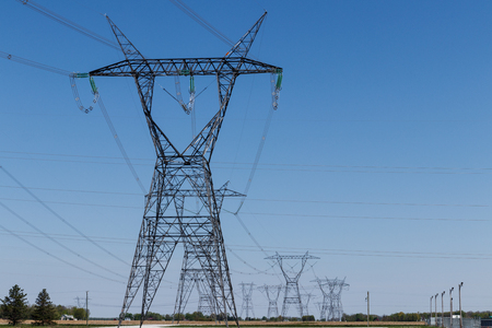 High-voltage power lines and pylon against blue sky I