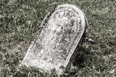 Fallen creepy headstone in a cemetery IV Stock Photo