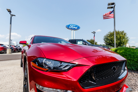 Fishers - Circa August 2018: Ford Mustang at a dealership with American flag. Ford sells products under the Lincoln and Motorcraft brands