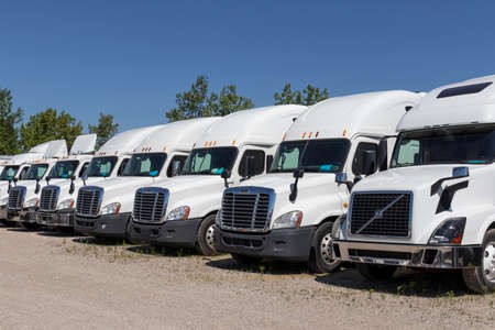 Indianapolis - Circa June 2020: Freightliner and Volvo Semi Tractor Trailer Trucks Lined up for Sale. Freightliner is owned by Daimler. Redakční