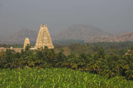 Virupaksha Temple, surrounded by palm plantations and mountains  View from mountain Matangi on sunrise, Hampi, Karnataka, India photo