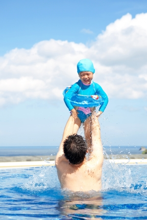 Father and Daughter  playing in swimming Pool photo