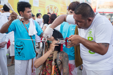 devotee: PHUKET, THAILAND - SEPTEMBER 29: An unidentified devotee of a Chinese shrine gets pierced on his mouth with sharp weapon to take part in the 2014 Phuket Vegetarian Festival on September 29, 2014 in Phuket, Thailand Editorial