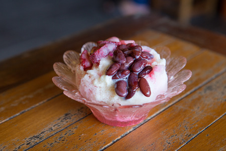 dessert topping: Traditional Asian shaved ice Dessert topping with red bean on wood table