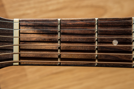 fretboard: guitar fretboard on blurred wood background light and shadow filter tone