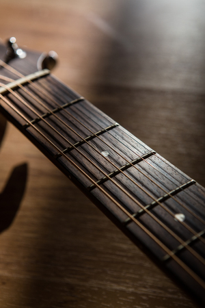 frets: guitar neck with string on blurred wood background light and shadow filter tone
