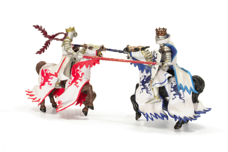 Joust of toy medieval knights. Isolated on white background