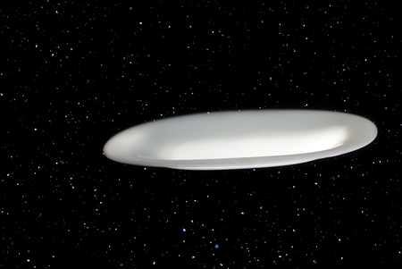 Mysterious flying saucer flies against a stellar background Stockfoto