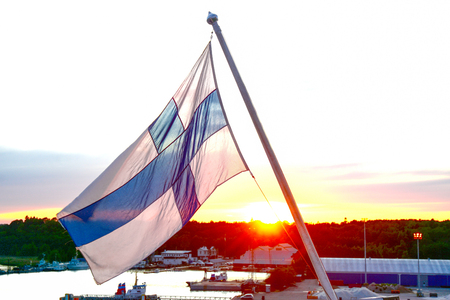 Finnish flag against the setting sun, in the evening at the port of Turku Stock Photo
