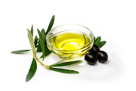 Glass bowl with olive oil, black olives and olive leafs. Close-up, isolated on white background