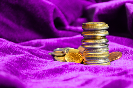 Stack of different European coins on purple velvet background. Close-up. Stock Photo