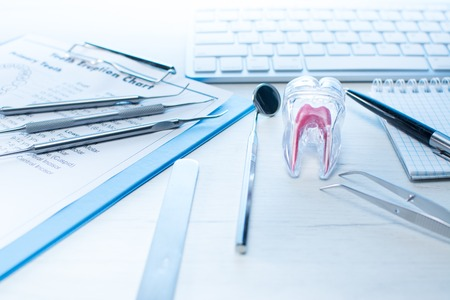 Dentist tools, tooth eruption chart and tooth model on table with computer keyboard and notebook. Dental probe, mirror and two explorers Dental hygiene - Education concept. Stock Photo