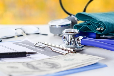 Stethoscope or phonendoscope, tonometer and medical insurance claim form with glasses and pen on doctor table in the office, medical concept of life planing. Autumn colors in window. Stock Photo
