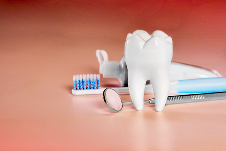 White big healthy tooth and different tools for dental care, on living coral gradient dental background.