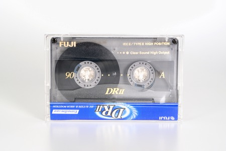PRAGUE, CZECH REPUBLIC - FEBRUARY 20, 2019: Audio compact cassette Fuji DRII chrome 90 in plastic box. Audio cassette on a white background. Analog format for audio playing and recording.