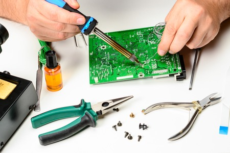 The electronics technician replaces the non-working element of the electronic device with a soldering iron. The hands of an electronics engineer. Repair electronic devices concept.
