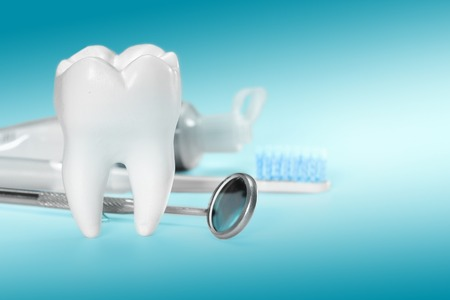 White big healthy tooth and different tools for dental care. On gradient dental background. Stock Photo