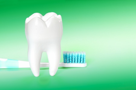 White big healthy tooth and toothbrush for dental care. On green gradient dental background. Stock Photo