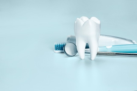 White big healthy tooth, toothbrush and toothpaste for dental care. On light blue dental background.