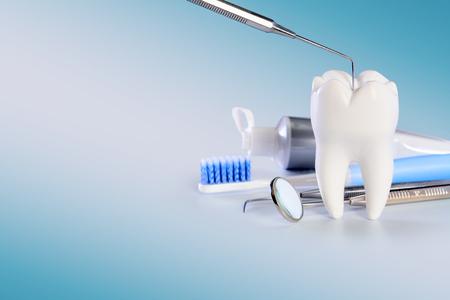 Grande dente sano bianco e strumenti diversi per le cure odontoiatriche. Su sfondo dentale sfumato con sonda dentale.