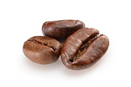 Granos de café. Vista macro de tres granos de café tostado, primer plano, aislado sobre fondo blanco.