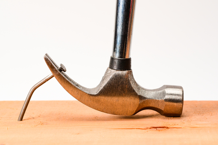 El extractor de clavos de martillo vintage saca un clavo grande doblado de la tabla de madera. Foto de archivo