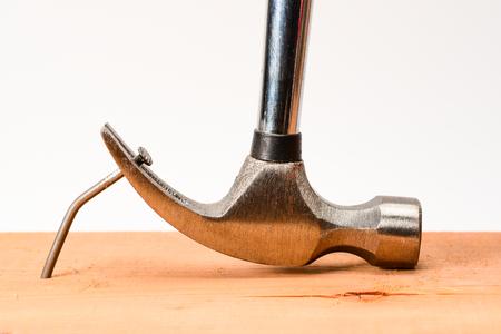 L'extracteur de clou de marteau vintage tire un gros clou plié de la planche de bois. Banque d'images