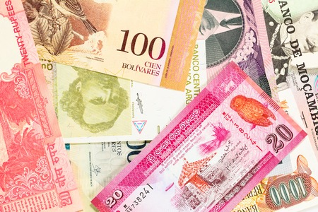 Old bills from different exotic countries. Colorful money background. Close-up macro. Imagens