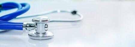 Estetoscopio o fonendoscopio en un escritorio blanco de médicos. Tratamiento del resfriado o la gripe, tamaño pancarta Foto de archivo