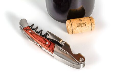 Professional sommelier or waiter knife, corkscrew and bottle opener close up macro. Closed, with bottle and cork. Archivio Fotografico - 127147619