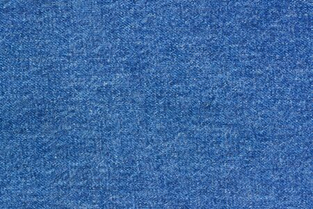 Jeans background denim pattern. Classic dark blue stonewashed fabric texture. Background of jeans canvas close-up.