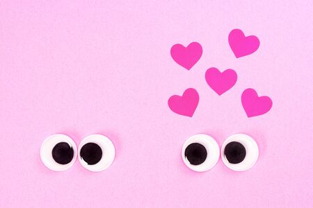 Googly eyes of strange pair of lovers, one of which cross-eyed, on rose background with some small hearts. Close up toy eyes.
