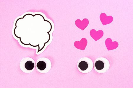 Googly eyes of strange pair of lovers on rose background with some small hearts and copy space for thoughts. Close up toy eyes. Фото со стока