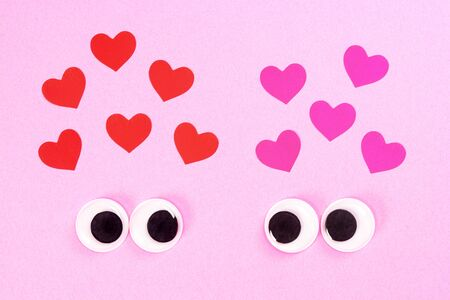 Googly eyes of strange pair of lovers on rose background with some small hearts. Close up toy eyes. Фото со стока