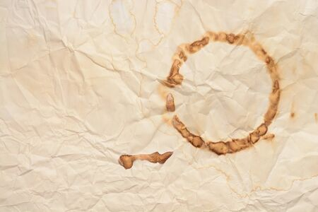 Vintage crumpled old paper background with spot from wet cup of coffee.